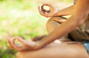 En kvinna sitter och mediterar. Man ser bara benen i lotusställning och händerna lagda på knäna.
