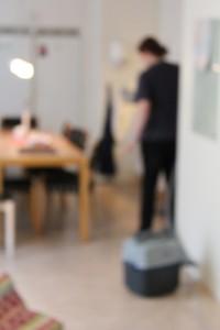 Oskärpt bild på kvinna som dammsuger ett kök.