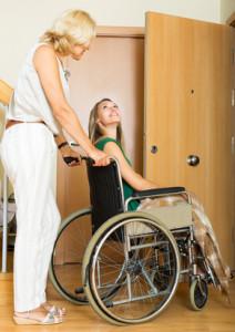 Kvinna kör annan kvinna i en rullstol. Hon i rullstolen tittar upp på hon som kör och ler.
