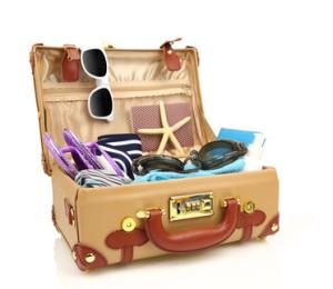 Öppen resväska av äldre modell, packad med många saker.