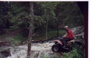 Anders på en fyrahjuling på väg över en fors i en skog.