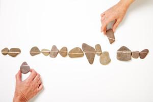 Händer lägger ut stenar med ett vitt sträck. Flera stenar på rad skapar en vit linje.