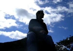 En ensam man sittande på en sten, sett snett nerifrån. Mannen i siluett mot en himmel med några vita moln.