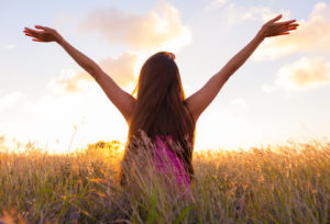 Kvinna på äng med händerna uppsträcka i luften
