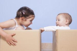 Två barn som leker i kartonger